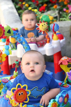 Two baby boys twin brothers playing together