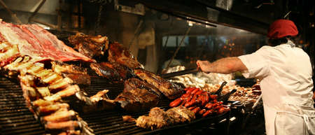 Argentinian chef cooking meat in the restaurant Stock Photo