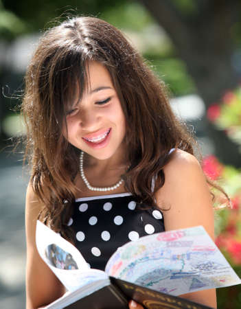 Happy girl reading a book on a sunny day