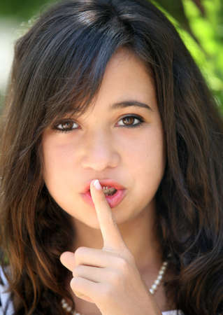 A pretty teenage girl doing be quiet gesture photo