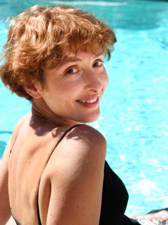 Mooie rijpe vrouw lachend bij het zwembad