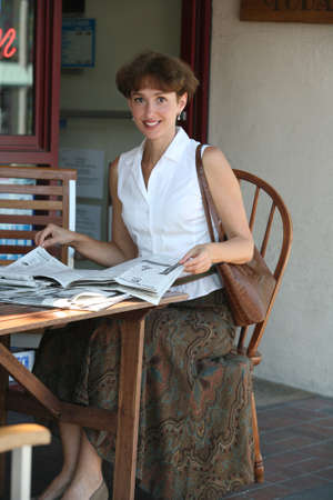 citylife: Mature woman reading newspaper in a cafe Stock Photo