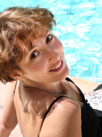 ordinary woman: Pretty mature woman smiling by the pool