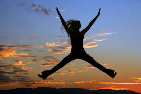 jubilate: Silhouette of a jumping woman at sunset Stock Photo