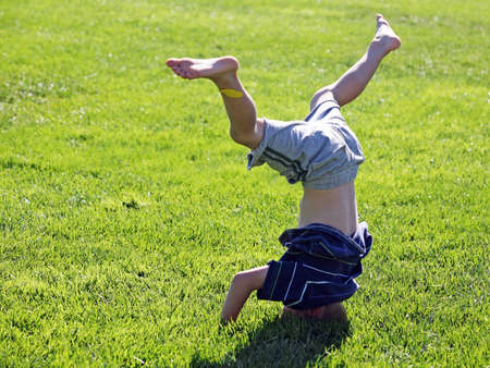 Little boy standing on his head on a grass photo