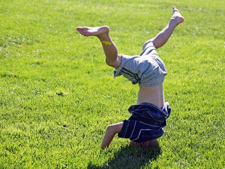 ni�o parado: Poco muchacho de pie sobre su cabeza sobre un c�sped