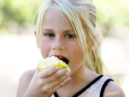 A funny blond girl eating an apple photo