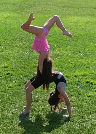 beautiful preteen girl: Two little girls exercising in the park Stock Photo