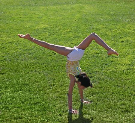Teen girl doing a handstand on a grass