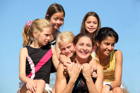 Woman laughing and five girls around her photo