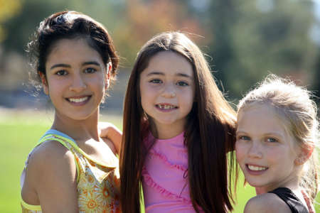 Three pretty girls of different ages and races smiling  Stock Photo