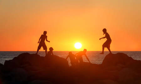Boys playing on the beach at sunset Stock Photo