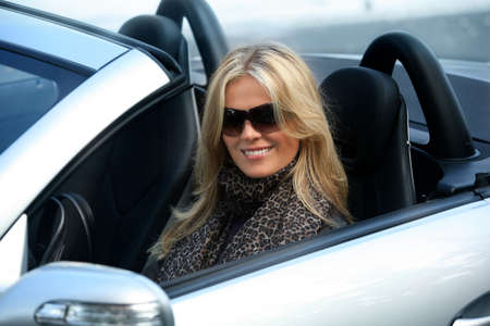 Blond girl in sunglasses driving convertable car Stockfoto