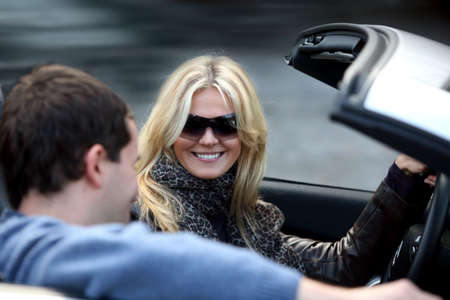 sportcar: Blond woman and a man in a convertible car