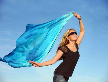 Beautiful blond woman running with a blue scarf photo