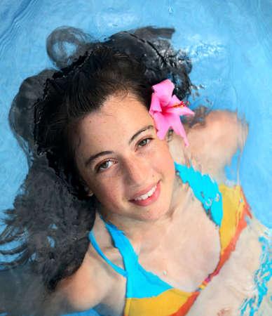 beach babe: Pretty teen ragazza con un fower in una piscina