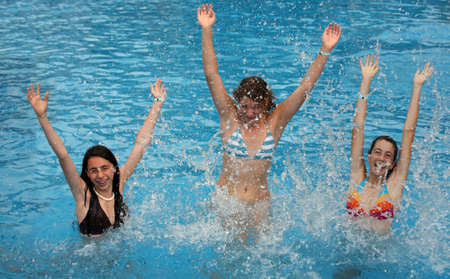 splash pool: Three young girl jumps in the pool