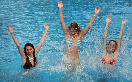 enfant maillot: Trois jeune fille saute dans la piscine  Banque d'images