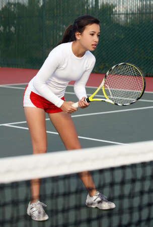 A teenage girl playing tennis
