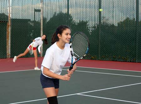 Two girls playing tennis