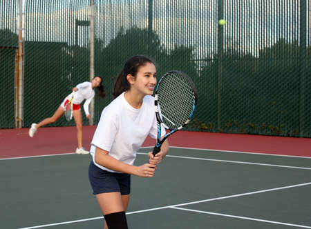 teens playing: Two girls playing tennis