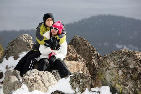 Happy young couple on the top of the mountain in winter photo