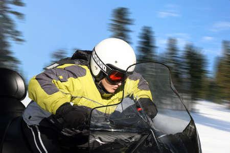 A young man riding a snowmobile Stock Photo