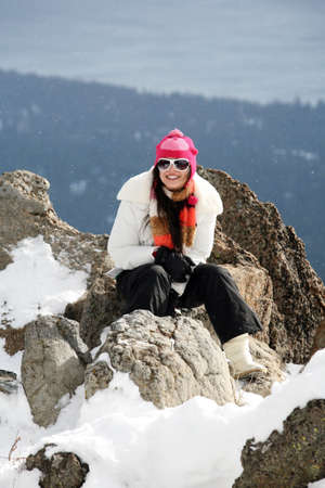 Happy young girl on the top of the mountain in winter photo