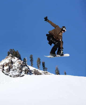 thrilling: Snowboarder jumping high at Lake Tahoe resort Stock Photo
