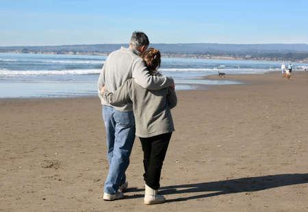 parejas caminando: Una pareja madura en la playa caminando