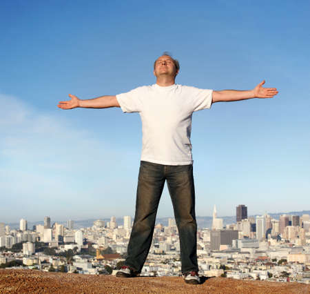 A man standing on a hill with a view of San Francisco, his arms raised.