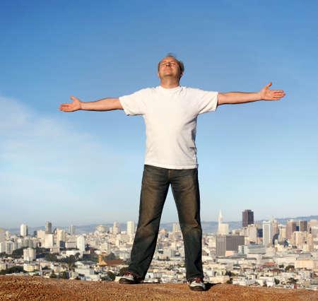 Een man staat op een heuvel met uitzicht op San Francisco, zijn armen naar voren.