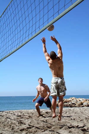Young men playing volleyball on the beach
