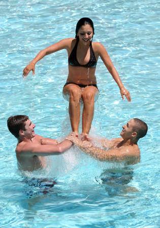 splash pool: Tres adolescentes feliz jugando en la piscina  Foto de archivo