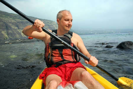activ: Mature man kayaking in the ocean on Big Island, Hawaii
