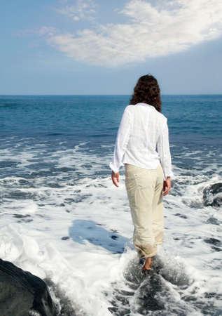 Woman standing on a black sand beach on Big Island, Hawaii photo