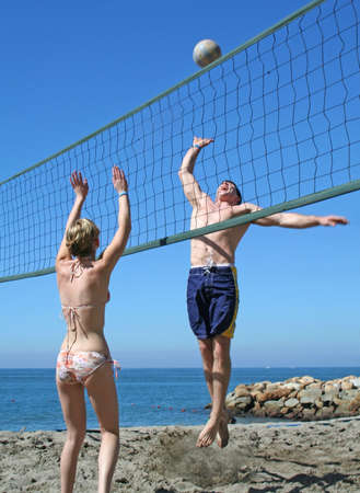 Young people playing volleyball on the beach photo