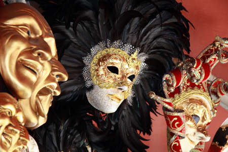 drama mask: Venetian masks with black feathers on a red background
