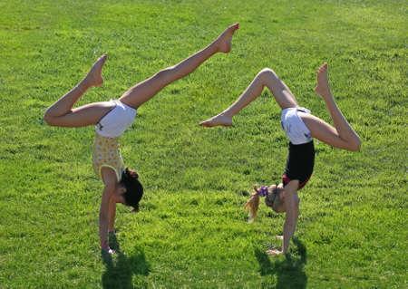 Teen girls doing a handstand on a grass Stock Photo
