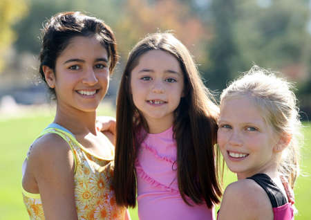 Three smiling girls of different race and age Stock Photo
