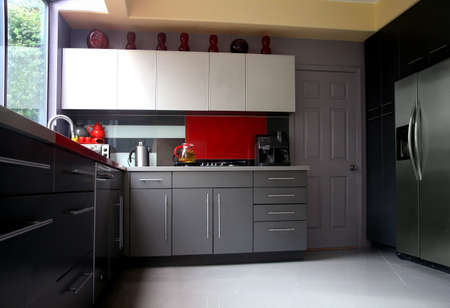 A modern kitchen with gray cabinets and glass backsplash