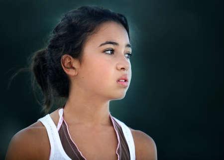 An unhappy teenage asian girl looking sideways photo