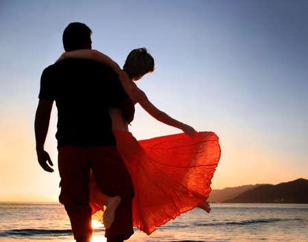 familia viaje: Una pareja disfrutando de la puesta de sol en la playa