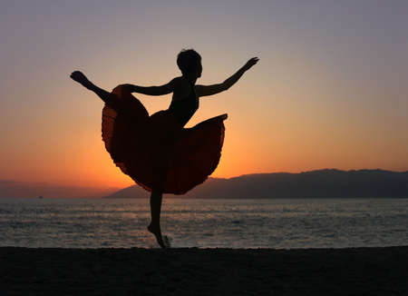 Dramatic image of a woman dancing by the ocean at sunset, silhouette