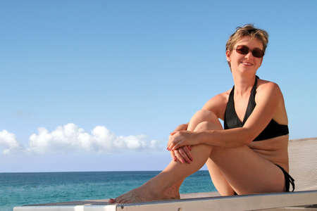 A happy mature woman relaxing on a beach by the ocean photo