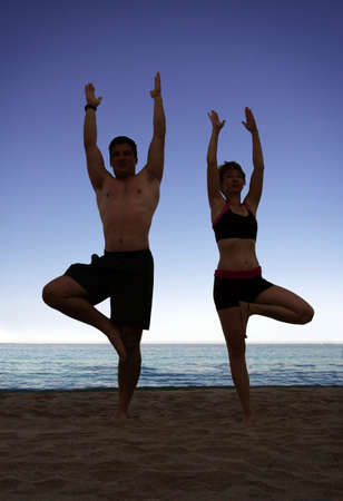 Couple doing yoga exercise on the beach photo