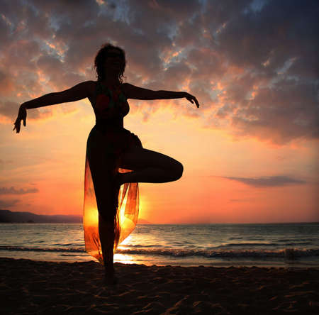 Woman doing yoga exercise on the beach at sunset, silhouette
