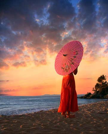 A woman in orange skirt walking on a beach Stockfoto