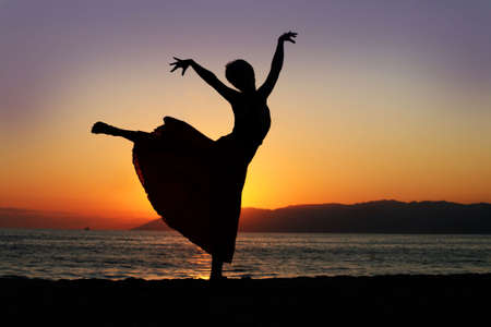Dramatic image of a woman dancing by the ocean at sunset, silhouette Stock Photo - 3990209