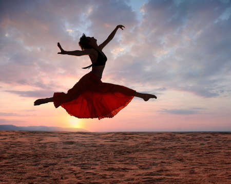 outstretched: Dramatic image of a woman jumping above the ocean at sunset, silhouette Stock Photo